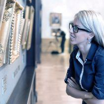 Woman looking at old paintings in art gallery